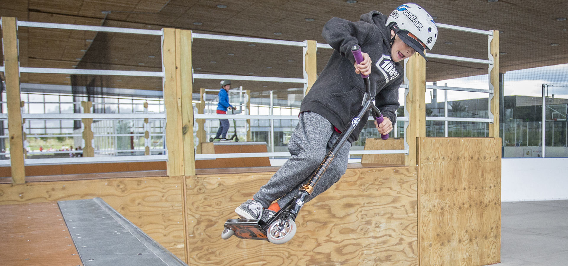 Boy on scooter jumping off skatepark