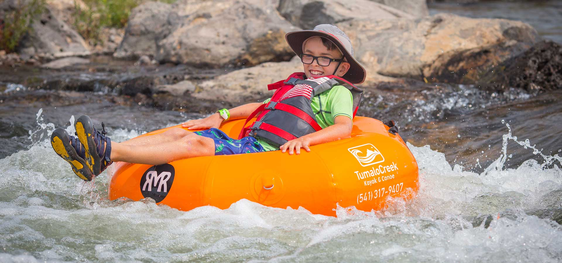 Boy on tube floating through rapids