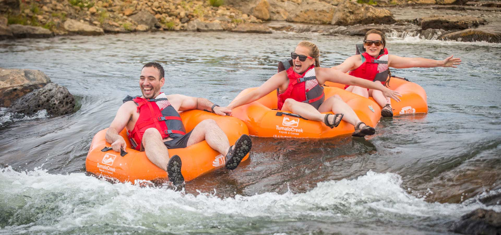 Group on tubes floating through rapids
