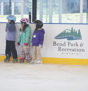 Image of children learning to ice skate in front of an ice rink dasher board at The Pavilion.