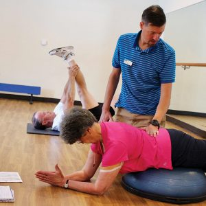 Image of fitness training helping a patron achieve their fitness goals.
