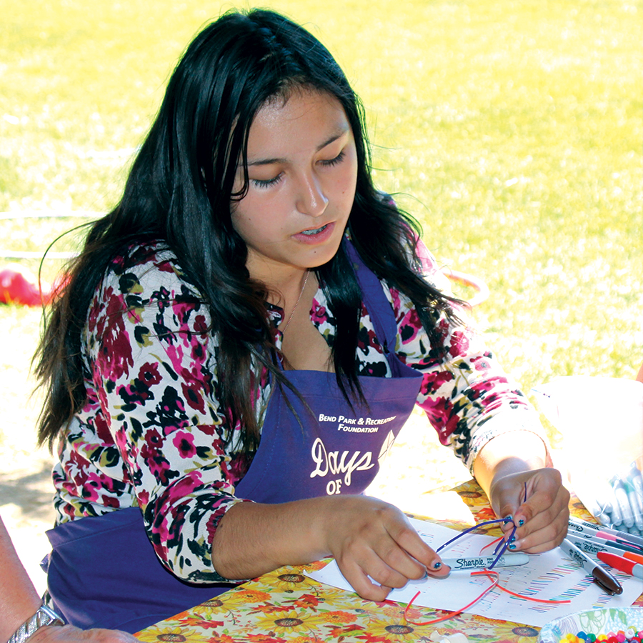 Image of a teen volunteer assisting at a free community event.
