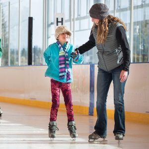 Image of a family skating at a public open skate session at The Pavilion in Bend.