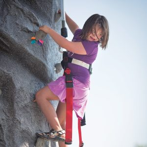 Image of a young lady rock climbing with a Therapeutic Recreation program.