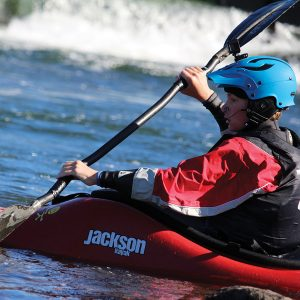 Image of a kid in a whitewater kayak in the Bend Whitewater Park.