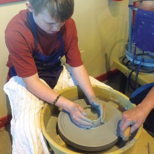 Image of a kid's hand thrown pottery class at the Art Station.