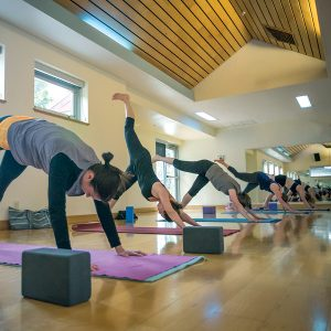 Image of a Yoga class in the Mind & Body Studio at Juniper Swim and Fitness Center.