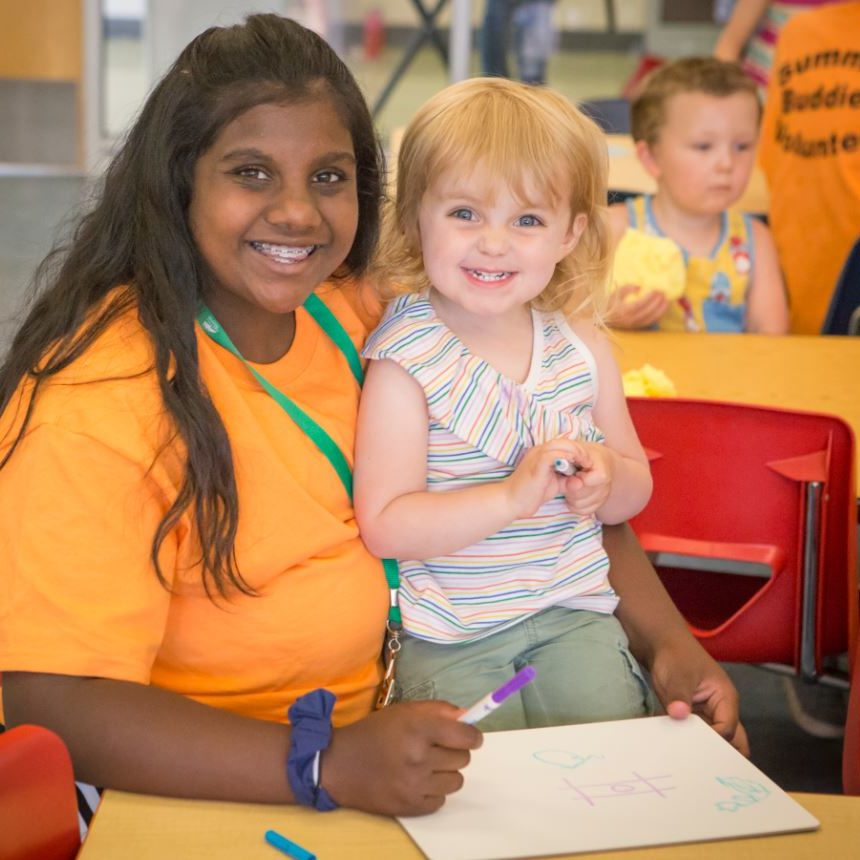 Image of a teen volunteer at Summer Buddies childcare at Juniper.