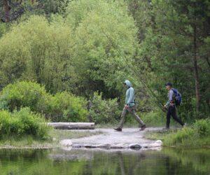 Hikers crossing Tumalo Creek in Shevlin Park